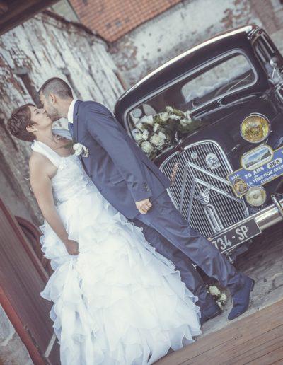 Mariés s'embrassent devant la voiture